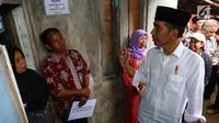 Presiden Joko Widodo berbincang dengan warga saat meninjau rumah yang dipasang listrik gratis di Kampung Pasar Kolot, Garut, Jawa Barat, Jumat (18/1). Pemasangan listrik gratis di Jawa Barat dialkuaknmelalui sinergi 34 BUMN. (Liputan6.com/Angga Yuniar)