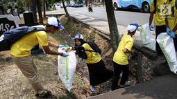 Sejumlah relawan membersihkan sampah di kawasan Taman Mini Indonesia Indah (TMII), Jakarta, Sabtu (15/9). Gerakan World Cleanup Day 2018 yang digelar Indofood bertujuan meningkatkan kesadaran masyarakat menjaga lingkungan. (Liputan6.com/Fery Pradolo)