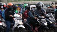 Pengendara motor di pemberhentian lampu Merah, Kota Depok, Jawa Barat, Minggu (12/4/2020). Menteri Kesehatan menyetujui menerapkan Pembatasan Sosial Berskala Besar (PSBB) di wilayah Kota Depok yang akan dimulai, Rabu (15/4) dalam pencegahan meluasnya COVID-19. (Liputan6.com/Helmi Fithriansyah)