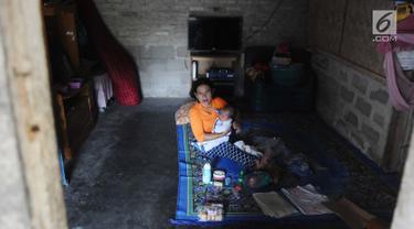 Seorang ibu menggendong sang anak saat santai di rumahnya dusun Regahan Lada, Pulau Sebesi, Lampung, Senin (31/12). Banyak warga dusun ini yang bertahan di lokasi pascatsunami yang melanda Selat Sunda pada 22 Desember lalu. (Liputan6.com/Herman Zakharia)