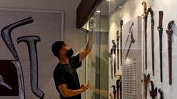 Seorang pekerja membersihkan etalase yang memajang keris jelang pameran persenjataan tradisional di Museum Aceh, Banda Aceh, Aceh, Jumat (15/10/2021). Pameran Senjata 2021 menampilkan 176 jenis senjata yang merupakan koleksi Museum Aceh. (CHAIDEER MAHYUDDIN/AFP)