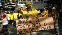 Seorang suporter menunjukan hasil akhir Brasil melawan Kosta Rika pada laga grup E Piala Dunia 2018 di Rio de Janeiro, Brasil, (22/6/2018). Brasil menang 2-0. (AP/Silvia Izquierdo)