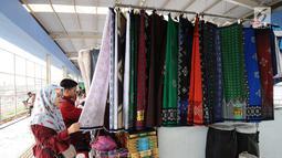 Pengunjung memilih sarung di skybridge Tanah Abang, Jakarta, Rabu (8/5/2019). Hari ketiga puasa bulan Ramadan, Warga Jakarta dan penyangga sekitarnya sudah mulai berbelanja pakaian muslim dengan harga yang murah untuk kebutuhan sendiri atau untuk dijual kembali. (Liputan6.com/Herman Zakharia)