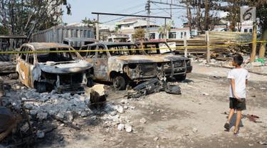 Seorang anak berjalan melintasi sejumlah mobil yang hangus terbakar di lahan parkir Jalan Budi Mulia Utara, Pademangan, Jakarta Utara, Rabu (24/7/2019). Kebakaran menghanguskan 14 mobil, 5 sepeda motor, dan 3 bedeng serta seorang warga mengalami luka bakar. (Liputan6.com/Immanuel Antonius)