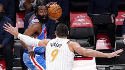 Pebasket Brooklyn Nets, James Harden, berusaha melewati pebasket Orlando Magic, Nikola Vucevic, pada laga NBA, Sabtu (16/1/2021). Nets menang dengan skor 122-115. (AP Photo/Mary Altaffer)