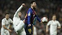 Striker Barcelona, Lionel Messi, berebut bola dengan bek Real Madrid, Sergio Ramos, pada laga La Liga di Stadion Santiago Bernabeu, Sabtu (2/3). Real Madrid takluk 0-1 dari Barcelona. (AP/Manu Fernandez)