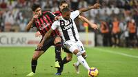 Pemain Juventus, Douglas Costa (kanan) berebut bola dengan pemain AC Milan, Lucas Paqueta (kiri) pada laga final di King Abdullah Sports City, Kamis (17/1). Juventus keluar sebagai kampiun dengan meraih kemenangan tipis 1-0. (Fayez Nureldine / AFP)