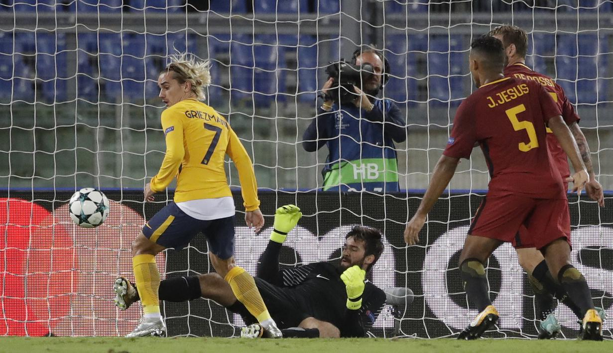 Kiper AS Roma, Alisson menghalau bola sepakan pemain Atletico Madrid, Antoine Griezmann pada laga grup C Liga Champions di Olympic stadium, Rome (12/9/2017). AS ROma bermain imbang 0-0 dengan Atletico. (AP/Alessandra Tarantino)
