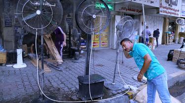 Seorang pria mendinginkan diri dari cuaca panas di bawah kipas angin di Baghdad, Irak, Kamis (1/7/2021). Pemerintah Irak menetapkan 1 Juli 2021 sebagai hari libur resmi di Baghdad karena gelombang panas yang menyengat. (AP Photo/Khalid Mohammed)