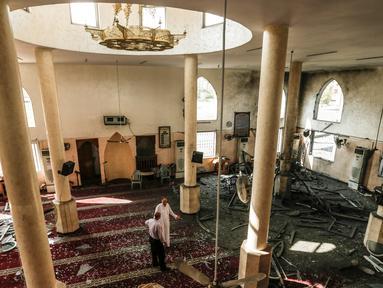 Dua pria memeriksa kerusakan masjid yang terkena serangan udara Israel di Kota Gaza, Palestina (15/7). Militer Israel mengatakan telah meluncurkan serangan udara yang menargetkan pasukan Hamas di Jalur Gaza, Sabtu (14/7) lalu. (AFP  Photo/Mahmud Hams)