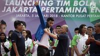 Direktur Pemasaran Pertamina Muchamad Iskandar (kedua kanan) mengenakan jaket kepada kapten tim putra Agung Seganti (tengah) saat Launching Tim Bola Voli Jakarta Pertamina Energi di Kantor Pusat Pertamina, Jakarta, Jumat (5/1).(Liputan6.com/Arya Manggala)