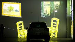 Orang-orang duduk di mobil mereka menikmati pameran seni Vincent Van Gogh di Toronto, Ontario, Kanada pada 3 Juli 2020. Pameran seni di masa pandemi Covid-19 mendatangkan ide kreatif para penyelenggara kegiatan dengan memamerkan hasil karya seni lewat konsep drive-in. (Cole BURSTON/AFP)