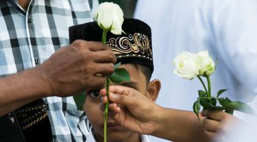 Umat Buddha Myanmar memberikan mawar putih kepada umat Islam yang akan melaksanakan salat Id pada perayaaan Idul Fitri di kota Than Lyin, pinggiran Yangon, Rabu (5/6/2019). Momen ini menjadi sebuah aksi solidaritas yang langka di sebuah negara, di mana Islam kerap difitnah.  (Sai Aung MAIN/AFP)