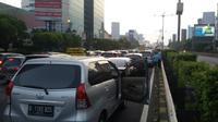 Akibat lalu lintas yang macet tak bergerak, sejumlah pengendara memilih keluar dari kendaraannya.