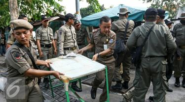 Petugas Satpol PP mengakut lapak pedagang ke atas mobil truk kdi kawasan Senen, Jakarta, Selasa (29/3/2016). Penertiban dilakukan karena lapak PKL yang berada di atas trotoar mengganggu pejalan kaki. (Liputan6.com/Yoppy Renato)
