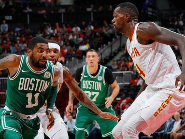 Pebasket Boston Celtics, Kyrie Irving, berusaha melewati pebasket Atlanta Hawks, Dewayne Dedmon, pada laga NBA di Philips Arena, Atlanta, Senin (6/11/2017). Hawks kalah 107-110 dari Celtics. (AFP/Kevin C Cox)