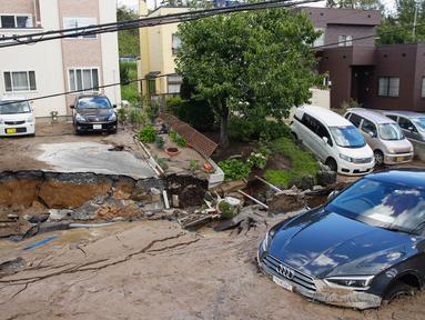 Sebuah mobil terjebak di jalan yang rusak akibat gempa mengguncang Sapporo di prefektur Hokkaido, pada Kamis (6/9). Gempa magnitudo 6,7 yang mengguncang Hokkaido kemudian memicu tanah longsor. (Hiroki Yamauchi/Kyodo News via AP)