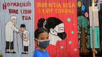 Seorang anak kenakan masker dengan latar belakang mural Indonesia Bisa Stop Corona di Lapangan Bulutangkis, Kampung Kali Pasir, Jakarta, Selasa (7/4/2020). Pesan mural mengajak warga untuk memutus rantai penyebaran Corona Covid-19 dengan diam di rumah. (Liputan6.com/Fery Pradolo)