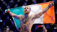 Conor McGregor mengibarkan bendera Irlandia setelah mengalahkan Donald 'Cowboy' Cerrone pada pertarungan kelas welter UFC 246 di T-Mobile Arena, Las Vegas, Amerika Sertikat, Sabtu (18/1/2020). McGregor mengalahkan Cowboy pada detik ke-40. (AP Photo/John Locher)