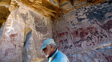 Arkeolog Jose Berenguer menunjukkan lukisan hewan llama di dinding batu cadas Gua Taira Calama, Chile, Minggu (21/7). Para penggembala meninggalkan sejumlah lukisan hampir tiga milenium lalu. (Martin Bernetti/AFP)