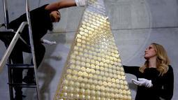 Karyawan dari rumah emas ProAurum menyusun koin emas yang disebut sebagai pohon Natal di Munich, Jerman, 3 Desember 2018. Pohon Natal ini terbuat dari 2.018 koin emas filharmonik wina ini memiliki berat 63 kilogram emas murni. (AP/Matthias Schrader)