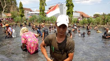 Salah satu warga berhasil menangkap ikan dalam kegiatan ngagogo untuk merayakan kesuksesan jagoan mereka dalam pilkades serentak Selasa lalu