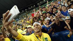 Neymar melakukan foto wefi bersama fans Brasil usai meraih medali emas pada final sepak bola melawan Jerman di Stadion Maracana, Rio de Janeiro, (21/8/2016) dini hari WIB. (AFP/Odd Andersen)