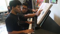 Instruktur mengajarkan seorang anak berkebutuhan khusus berlatih piano di Daya Pelita Kasih Center, Pejaten, Jakarta, Kamis (24/5). Di balik keterbatasannya, anak-anak autis memiliki bakat seni salah satunya bermain piano. (Liputan6.com/Arya Manggala)