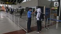 Petugas mengecek suhu tubuh calon penumpang di Terminal 1 A Bandara Internasional Soekarno Hatta, Tangerang, Sabtu (28/3/2020). PT Angkasa Pura II (Persero) akan membatasi kegiatan di Terminal 1 dan 2 Bandara Soetta mulai 1 April 2020 terkait meluasnya kasus Corona.  (Liputan6.com/Herman Zakharia)
