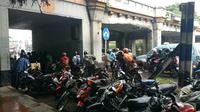 Hujan deras yang mengguyur Matraman menyebabkan sebagian pengendara motor berteduh di kolong jembatan (Liputan6.com/Nanda)