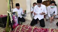 Presiden Jokowi berdoa di samping makam sang ibu. (Dok Agus Suparto/Setpres)