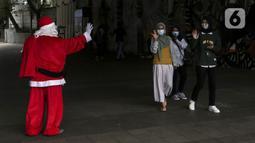 Pria berkostum Sinterklas menyapa pejalan kaki saat membagikan kopi gratis kepada warga di kawasan Jalan Jenderal Sudirman, Jakarta, Sabtu (19/12/2020). Pembagian kopi tersebut bertujuan untuk menyambut perayaan Natal 2020. (Liputan6.com/Johan Tallo)
