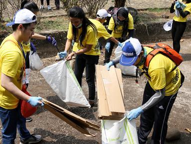 Relawan membersihkan sampah di kawasan Taman Mini Indonesia Indah (TMII), Jakarta. Kegiatan ini digelar dalam rangka World Cleanup Day 2018 yang bertujuan meningkatkan kesadaran masyarakat untuk menjaga lingkungan. (Liputan6.com/Fery Pradolo)