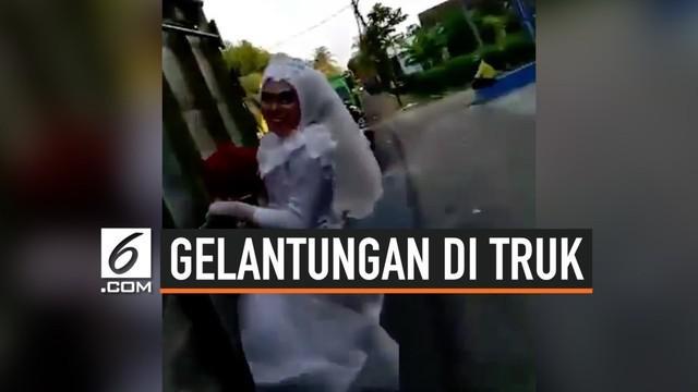 Sepasang pengantin melakukan aksi nekat yang mencuri perhatian warganet. Lengkap dengan pakaian pengantinnya, keduanya bergelantungan di sebuah truk yang sedang melaju.