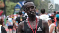 Pelari kenya Bernard Mwendia Muthoni usai menyelesaikan lari Full Marathon dalam Jakarta Marathon 2018 di GBK, Jakarta, Minggu (28/10). Bernard berhasil sampai finish kategori Full Marathon dalam catatan waktu 02:19:10. (Liputan6.com/Faizal Fanani)