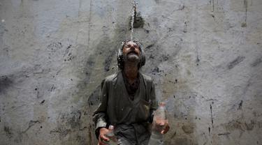 Seorang pria mendinginkan kepalanya di kucuran air keran usai mengisi botol saat cuaca panas yang ekstrem di Karachi, Pakistan, (23/6/2015). Gelombang panas yang telah menewaskan lebih dari 400 jiwa di kota selatan Pakistan. (REUTERS/Akhtar Soomro)