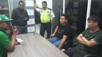 Kepolisian Polres Gorontalo mengamankan dua orang warga negara asing (WNA) asal Tiongkok yang bekerja di perusahaan tambang rakyat, Desa Ilangata, Kecamatan Anggrek, Gorontalo Utara. (Liputan6.com/Arfandi Ibrahim)