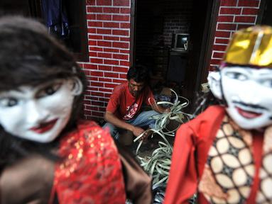Andri (42) membuat ondel-ondel di Jakarta, Selasa (19/3). Andri dan rekannya, Tarno memulai ide membuat miniatur ondel-ondel berbahan barang bekas seperti dari tali plastik, kardus, dan kain perca sejak 1 tahun lalu. (merdeka.com/ Iqbal S. Nugroho)