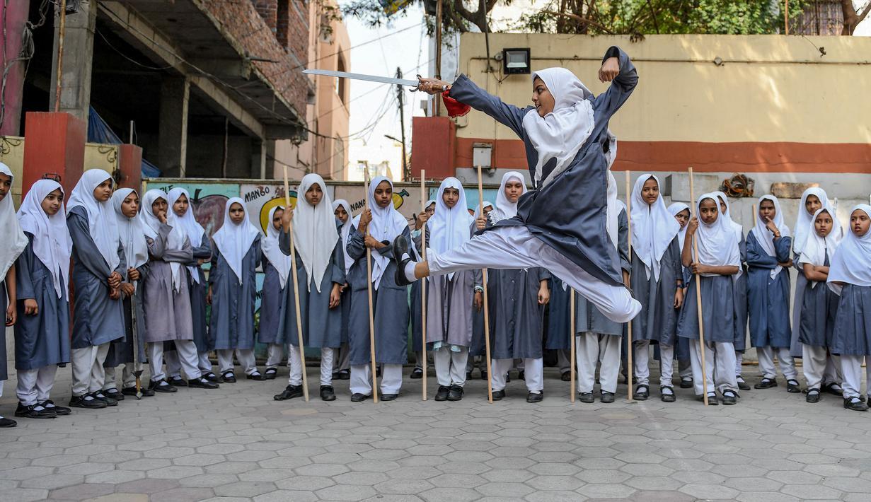 Seorang gadis muslim (tengah) memainkan pedang saat berlatih seni bela diri Vovinam untuk tampil dalam Hari Perempuan Internasional di sekolah menengah St Maaz, Hyderabad, India, Kamis (5/3/2020). Vovinam adalah seni bela diri menggunakan pedang dan tongkat asal Vietnam. (NOAH SEELAM/AFP)