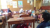 Nampak para siswa tengah berlindung dibawah meja saat simulasi mitigasi bencana diajarkan para mahasiswa (Liputan6.com/Jayadi Supriadin)