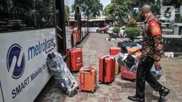 Petugas saat membawa barang-barang milik atlet kontingen DKI Jakarta saat tiba di Hotel Grand Cempaka Business, Jakarta, Kamis (14/10/2021). Para atlet dikarantina sebagai upaya pencegahan penyebaran virus Covid-19. (merdeka.com/Iqbal S. Nugroho)