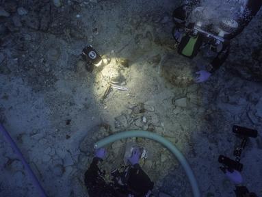 Tim arkeolog berada di samping sisa-sisa kerangka manusia yang ditemukan di dekat bangkai kapal era Romawi yang karam di perarian dekat Pulau Antikythera, Yunani, pada 6 September 2016. (Greek Ministry of Culture/Reuters)