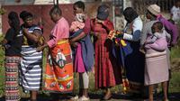 Warga antre untuk menerima sayuran dari komunitas Jan Hofmeyer di Vrededorp, Johannesburg, Afrika Selatan, Kamis (30/4/2020). Afrika Selatan akan mulai mengurangi penerapan lockdown ketat secara bertahap pada 1 Mei, meski kasus COVID-19 yang dikonfirmasi terus meningkat. (AP Photo/Jerome Delay)