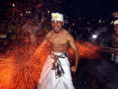 Seorang pria Bali dipukul dengan daun kelapa yang menyala saat ritual Lukat Gni di Klungkung, Bali (16/3). Tradisi lukat gni ini berasal dari dua kata yakni 'lukat' dan 'gni', malukat atau pembersihan, gni artinya api. (AP Photo / Firdia Lisnawati)