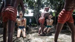 Seorang wanita berjalan di dekat patung-patung yang menggambarkan nasib orang-orang yang melakukan perbuatan buruk di taman yang menggambarkan neraka versi Buddha di kuil Wat Saeng Suk di provinsi pantai Thailand Chonburi (9/7/2020). (AFP/Lillian Suwanrumpha)