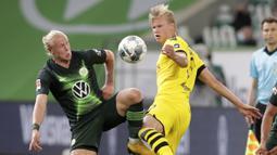 Pemain Borussia Dortmund, Erling Haaland, berebut bola dengan pemain Wolfsburg, Xaver Schlager, pada laga Bundesliga, Minggu (24/5/2020). Borussia Dortmund menang 2-0 atas Wolfsburg. (AP/Michael Sohn)
