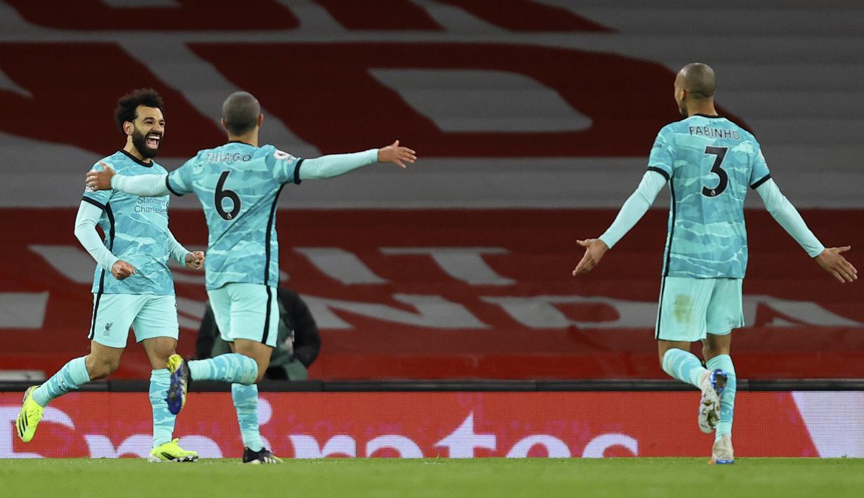 Pemain Liverpool Mohamed Salah (kiri) merayakan dengan rekan satu timnya setelah mencetak gol ke gawang Arsenal pada pertandingan Liga Inggris di Emirates Stadium, London, Inggris, Sabtu (3/4/2021). Liverpool membantai Arsenal dengan skor 3-0. (Julian Finney/Pool via AP)