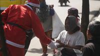 Hendayana, pendiri komunitas profesi badut Nyentrik Cimahi Bandung Sauyunan (Necis) mengenakan kostum Sinterklas membagikan makanan gratis di Kota Cimahi, Jawa Barat, Jumat (25/12/2020). (Liputan6.com/Huyogo Simbolon)