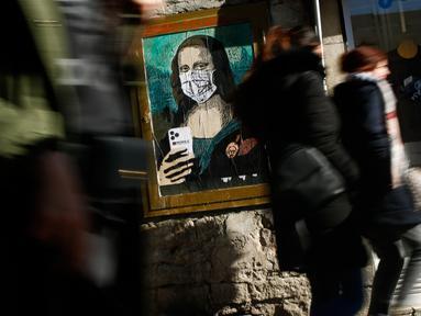 """Orang-orang berjalan melewati poster seniman Italia Salvatore Benintende yang menggambarkan Mona Lisa karya Leonardo da Vinci mengenakan masker dan memegang smartphone yang bertuliskan """"Mobile World Virus"""" di sebuah jalan di kota Barcelona, Spanyol pada Selasa (18/2/2020). (PAU BARRENA/AFP)"""