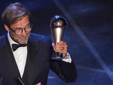 Pelatih Liverpool, Jurgen Klopp mengangkat trofi Pelatih Terbaik Dunia 2019 versi FIFA saat memberi sambutan di teater La Scala Milan, Italia utara (23/9/2019). Klopp menyabet mengalahkan Pep Guardiola dan Mauricio Pochettino. (AFP Photo/Marco Bertorello)